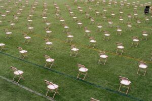 Afbeelding van een veld met stoeltjes op afstand van elkaar.
